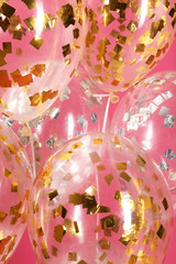 Balloons with sparkles on color background, closeup