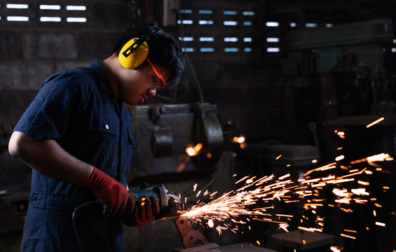 Mechanical engineer worker wearing safety equipment and operating a angle grinder on his workbench with metal held in an iron vice in a low light workshop with flash sparks