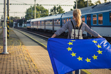 Travel by train. Backpacker woman with EU flag standing on railroad station