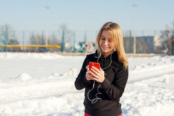 Portrait of a cute blonde girl listening to music while walking down the street holding a red phone in hand. Snow lies around