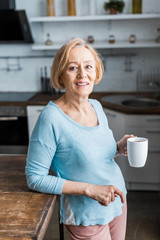 smiling senior woman with cup of coffee looking at camera in kitchen