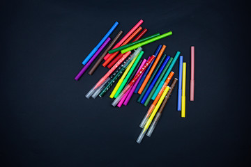 colored markers on a black background