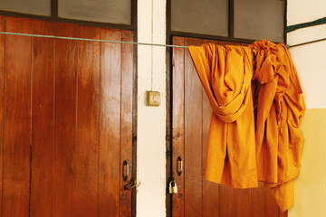 Monk's orange cloth hung on cloth line in Thai Buddhist temple.