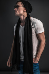 Young men model tests in studio.  Fashion shooting beautiful guy in blue jeans, white shirt, black scarf, hat and glasses. Posing on a gray background.