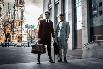 Two fashion men models posing on city street. Wearing in classic and casual closes. Suit, coat, shirt, sweater, boots and leather bag. Men model test near business center Wall mural