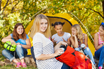 Cute girl holds red bag sitting near camping place