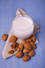 almond milk in the glass, and on the table colored blue, almonds with and without shell