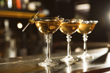 Glasses of martini cocktail with olives on bar counter. Space for text