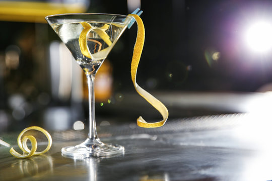 Glass of lemon drop martini cocktail on bar counter. Space for text