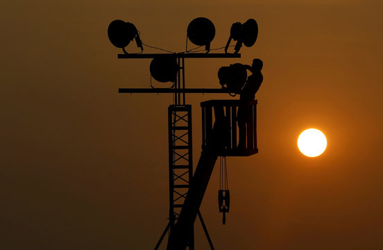 A man removes light bulbs on a temporary lamppost after an event in Colombo