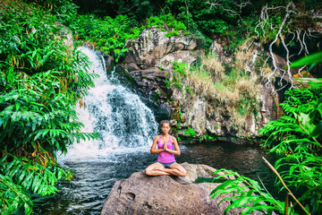 Yoga retreat woman praying doing the lotus pose meditating at waterfall forest in Kauai, Hawaii. Spiritual girl doing meditation in tranquil serenity nature. Tropical travel destination.