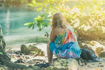 Back view of Female tourist is resting at Erawan Waterfall in Kanchanaburi, Thailand