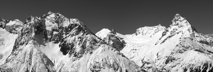 Wall Mural - Black and white panorama of snowy covered mountain peaks