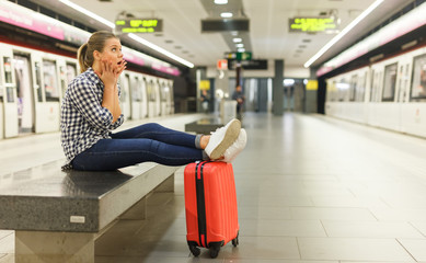Girl sitting with legs on suitcase at metro station