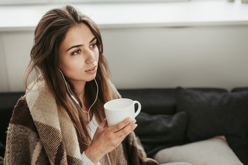 Calm and thoughtful girl has brown blanket around her shoulders. She holds white cup. Girl is listening to music. She is very peaceful