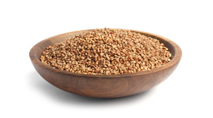 Bowl with uncooked buckwheat on white background