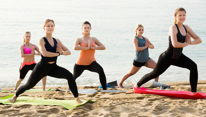 Glad sporty women practicing yoga positions