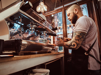 Handsome tattooed barista with stylish beard and hairstyle working on a coffee machine in a coffee shop or restaurant