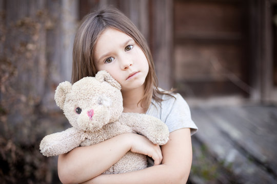Little Girl Holding Ragged Teddybear Outside - Poverty, Homelessness