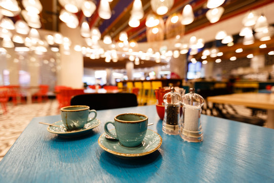 A cup of coffee on a saucer with a spoon stands on a blue table. Cup in focus. The background of the cafe is blurred.