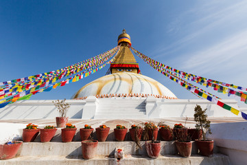 Boudhanath in Nepal. Cultural heritage in Kathmandu. The Biggest Tibetan temple. Nepalese prayer flags. Bottom on the steps pots of flowers