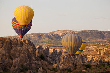 Poster Montgolfière / Dirigeable Many colorful hot air balloons flight above mountains - panorama of Cappadocia at sunrise. Wide landscape of Goreme valley in Cappadocia