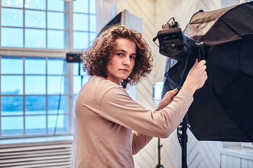 Photo of a curly handsome photographer in a studio looks into the camera and adjusts the light