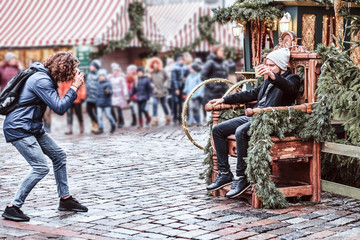 Young photographer in the city square where the kids are walking, photographing a friend sitting on a wooden throne, posing and drinking coffee