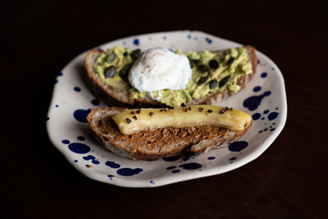 avocado toast with poached egg and almond buttered toast with fried banana