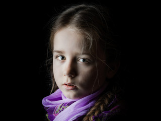 Beautiful little girl portrait on black background, seriously child