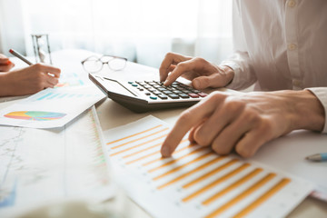 The hands of an accountant prepare a financial report on a calculator.  Wall mural