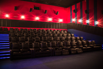 Empty cinema, cinema with soft chairs before the premiere of the film. There are no people in the cinema. Sliding automatic comfortable large leather chairs. Noise, no focus