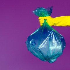 A woman's hand in a rubber glove holds a transparent green garbage bag with empty plastic bottles. The concept of ecology, separate waste collection and recycling.