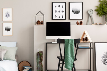 Cones on shelf above desk with all in one computer and wooden triangle , real photo with posters on grey wall
