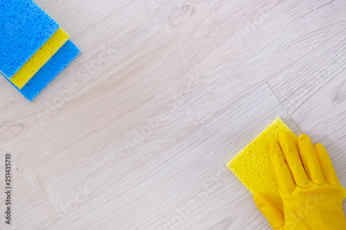 98d1991700c17 Hand in yellow rubber protective glove cleaning parquet floor with rag at  home. Housework and housekeeping concept.