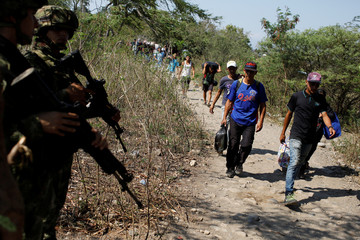 People carrying their belongings walk past Colombian army members in a pathway near the Colombian-Venezuelan border in the outskirts of Cucuta