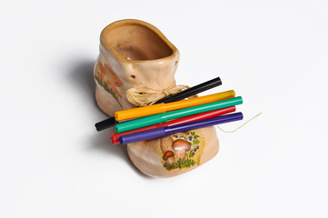 Closeup colorful pencils in boot shaped bowl. Closeup colorful pencils isolated on white background. Back to school concept