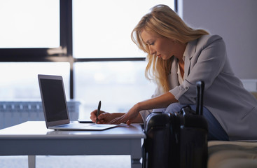 Businesswoman working on laptop in airport lounge