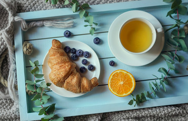 Croissant and cup of tea on wooden tray