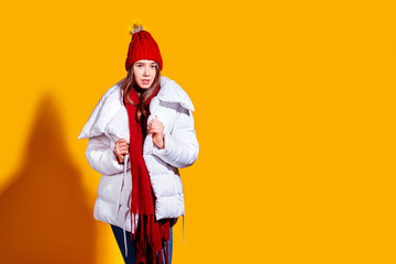 Stylish young woman in a white down coat and knite red hat on yellow background in studio.