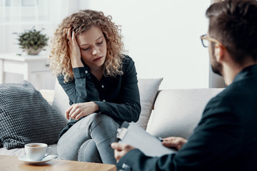 Blonde overwhelmed businesswoman sitting on the couch in psychotherapist office