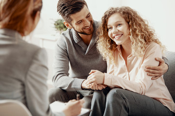 happy smiling husband and wife during therapy session with a psychologist