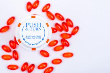 Docusate sodium red capsules and plastic container with Child-Resistant Push&Turn Cap. Top view.