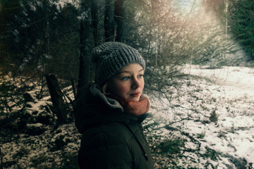 Woman with woolly hat in forest during winter