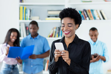 African american businesswoman sending message with phone