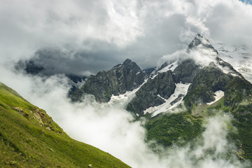 summer mountains green grass snow and stormy sky landscape