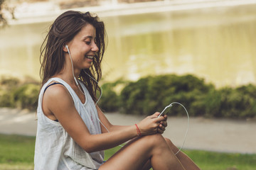 portrait of young woman listening to the music on the phone in the park
