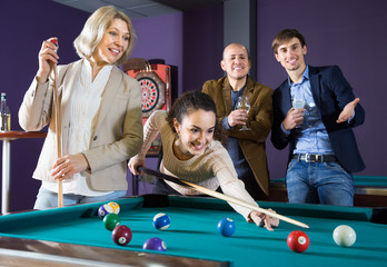 Group of friends playing billiards and smiling in billiard room