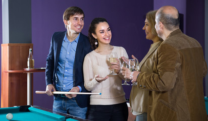 adult couples of different generations talk in the billiard room