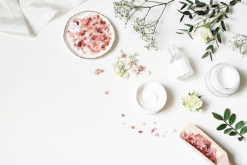 Styled beauty corner, web banner. Skin cream, tonicum bottle, dry flowers, leaves, rose and Himalayan salt. White table background. Organic cosmetics, spa concept. Empty space, flat lay, top view. Fotoväggar